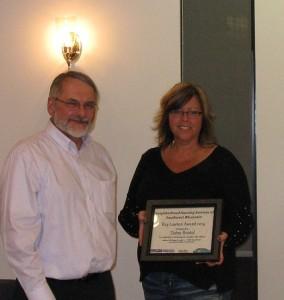 Barry Ziegahn, (L) NHSSW Board President awards Debra Bristol (R) the Ray Lawton Award